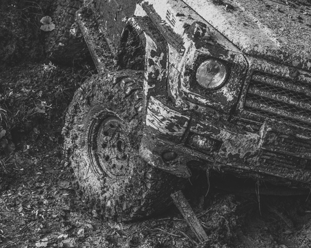 Dirty wheel of car after offroad race. SUV in autumn forest, fallen leaves. Car on country road covered with mud. Impassibility of roads concept. Stock Photo