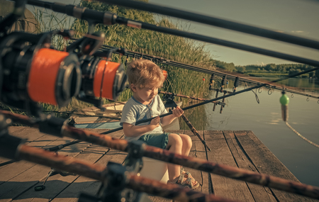 Baby sit on river pier with fishing rod and fishing Banco de Imagens