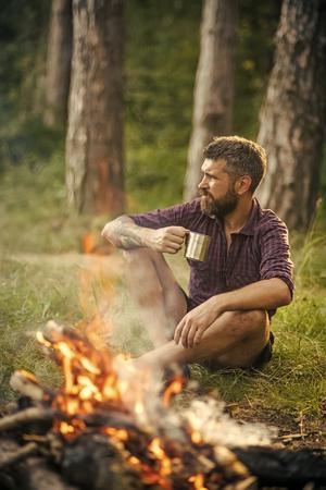 Man traveler drink tea at campfire flame