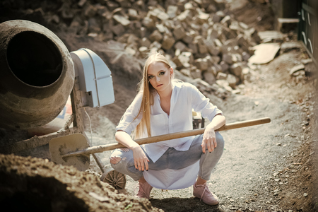 Beauty model with makeup at cement mixer. Woman worker in shirt and jeans on building site, fashion. Woman with long blond hair, hairstyle hold shovel. Fashion girl work at construction, vogue Standard-Bild