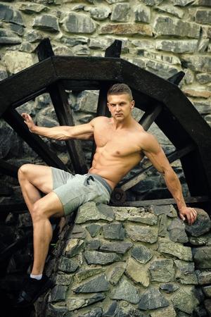 Man sit on stone at wooden wheel