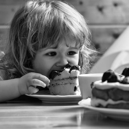 small boy eats strawberry cake