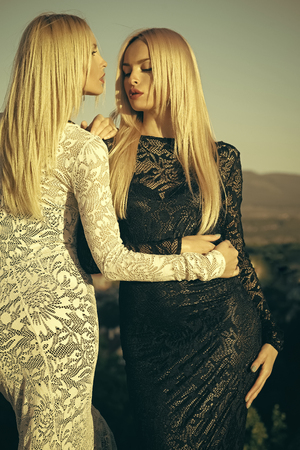 Two girls with long blond hair in lace dresses