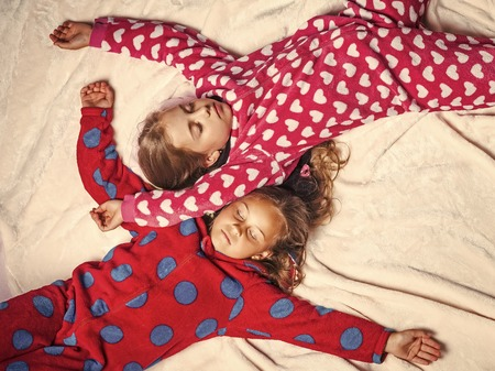 Girls in pajamas sleep in bed, top view Stockfoto