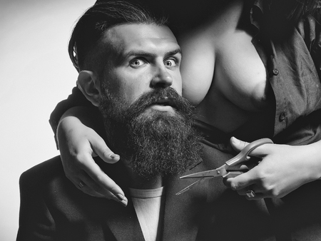 bare woman cutting male beard Stock Photo