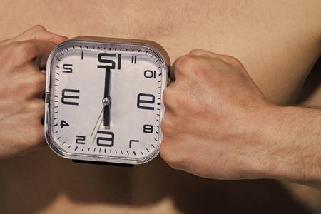 Alarm clock show six oclock between male fists Stockfoto