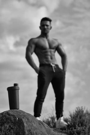 Mens heals body care. Muscular man posing near water bottle Фото со стока