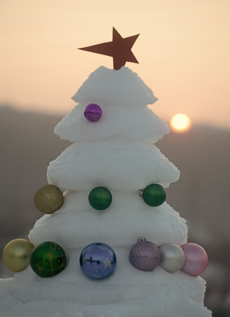 Christmas tree with baubles on sunset sky Banco de Imagens