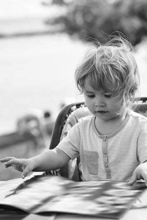 Cute baby boy reads menu card Stock Photo