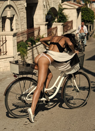Sexy girl with naked buttocks rides bicycle, urban background. Attractive brunette sit on bicycle. Fit and slim girl on sunny day travelling by bicy le. Sexy tourist concept.