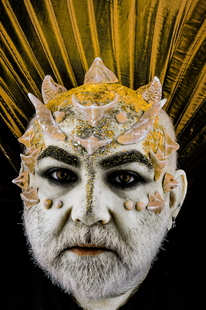 Head with thorns or warts, face covered with glitters, close up. Demon with golden collar, black background. Alien, demon, sorcerer makeup. Fantasy concept. Senior man with beard, with monster makeup. Stock Photo