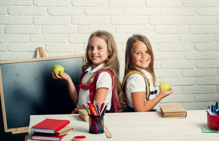 School time of girls. Little girls eat apple at lunch break. Back to school and home schooling. Friendship of small sisters in classroom at knowledge day. Happy school kids at lesson in september 1.