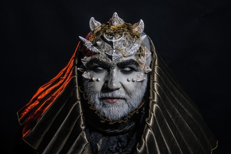 Senior man with white beard dressed like monster. Fantasy concept. Man with thorns or warts, face covered with glitters. Demon with golden hood on black background. Alien, demon, sorcerer makeup.