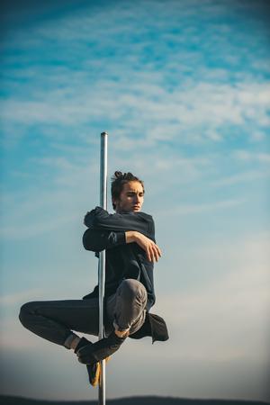 Athletic guy make acrobatic elements on pylon. athletic man sit on pole Imagens - 104607902