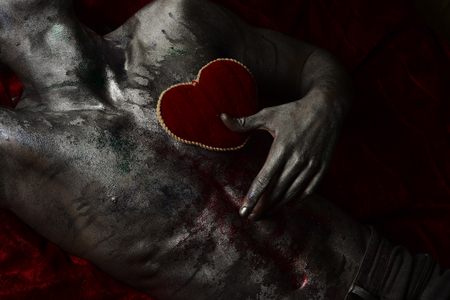 Valentines day concept. Male chest covered with shimmering silver paint and colorful glitters. Nude torso with red plush soft heart toy, dark background. Depression, loneliness, love, sadness.