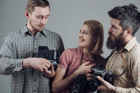 Men, woman on smiling faces looks at camera, grey background. Men in checkered clothes, retro style. Company of busy photographers with old cameras, filming, working. Vintage photographer concept. 스톡 콘텐츠