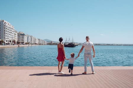 Love and trust as family values. Mother and father with son look at bay with ship. Child with father and mother. Summer vacation of happy family. Family travel with kid on mothers or fathers day Banco de Imagens