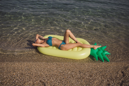 Maldives or Miami beach water. Girl sunbathing on beach with air mattress. Summer vacation and travel to ocean. Sexy woman on Caribbean sea in Bahamas. Pineapple inflatable mattress, activity and joy