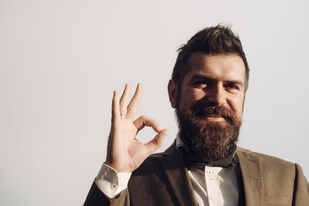 Happy guy show ok sign on grey sky. Bearded man smile with hand gesture outdoor. Businessman smiling with beard and and mustache on unshaven face. Agreement and approval, copy space.