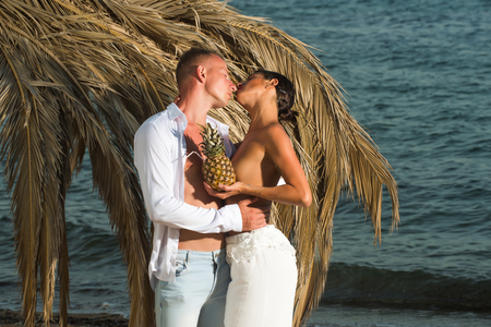Colorized vintage outdoor portrait of beautiful romantic couple of topless girl and muscular guy in jeans kissing with pineapple on beach
