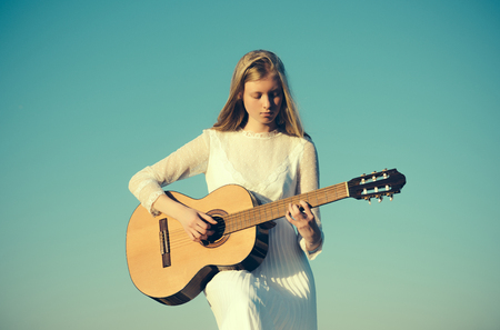 Fashion musician in white dress on sunny nature. Woman guitarist perform music concert. Albino girl hold acoustic guitar, string instrument. Sensual woman play guitar on blue sky.