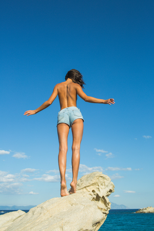 Freedom traveler woman standing topless with raised arms on the top of mountain and enjoy the beautiful of seascape. travel and freedom.