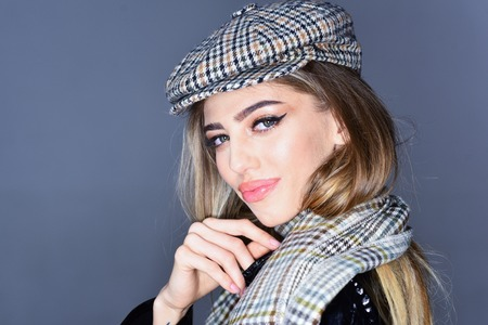 Woman on smiling face with make up with checkered accessories. Fashion accessories concept. Sexy lady in stylish outfit, close up. Girl with long hair wears kepi, scarf, grey background, copy space. Stock fotó