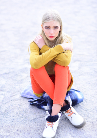 Blond girl sitting on blue folded parka on the street. Young female hipster posing on street.