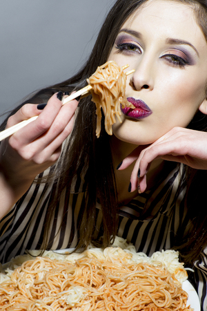 Young beautiful woman eating spaghetti on plate. Archivio Fotografico - 108381348