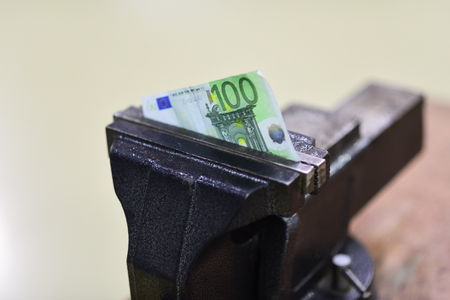 Hundred euro banknote squeezed in vise. Vise tool fix paper money on workbench. Euro currency devaluation or inflation and default. Finance and banking crisis. Economy and business problem. Stock Photo