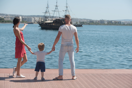 Mother and father with son look at bay with ship. mother and father hold hands of kid son and look on ship