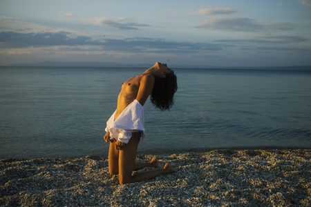 Sexy woman sit on sand with chest in sunset. Summer holidays and paradise travel vacation. woman at sea sunrise. sensual girl with body relax on beach. nature and environment. Stock fotó
