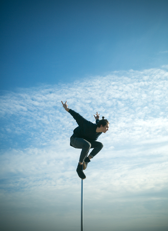 Strong man dancer workout on pole. Young man dancing on pylon. Sexy macho man fly on blue sky background. Pole dance sport. Athletic guy make acrobatic elements on pylon. Morning work out Stock Photo