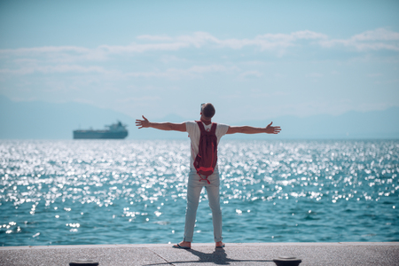 man traveler with backpack hold rised hands at sea water. travel and wanderlust concept. summer vacation and adventures. young man is going to marine trip. futute life and freedom concept. Stock Photo