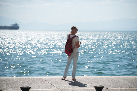 man traveler with backpack looking far away at sea water. travel and wanderlust concept. summer vacation and adventures. young man is going to marine trip. futute life concept. Banco de Imagens