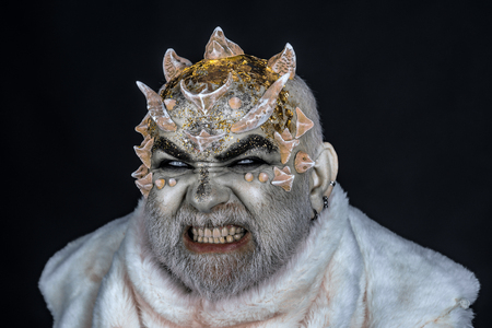 Demon on black background, close up. Man with thorns or warts in fur coat. Alien, demon, sorcerer makeup. Dark arts concept. Senior man on angry face with white beard dressed like monster. Standard-Bild