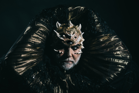Alien, demon, sorcerer makeup. Man with third eye, thorns or warts. Demon with golden collar on black background. Horror and fantasy concept. Senior man with white beard dressed like monster. Stock Photo