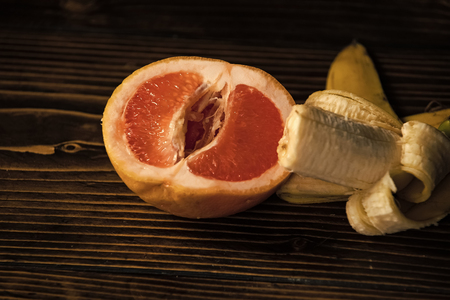 banana with yellow peel in red grapefruit