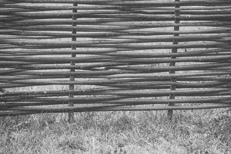 Fence of wooden twigs on green grass