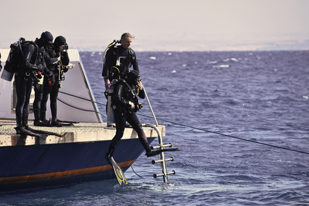 Divers jump from boat in blue sea water in Egypt Редакционное