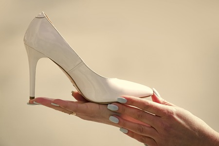 hand with glamour female shoe white color leather Stock Photo