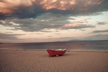 Fishermens boat at seacoast, on sand at sunset with horisont sea on background. Background of sea with waves and sky with clouds after storm. Fishing boat on beach in evening. Travel and rest concept. Stock Photo