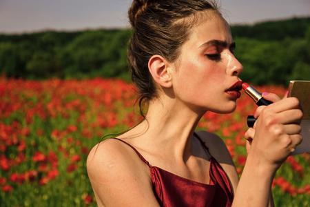 La giovane donna nel campo dei fiori di papavero, giovinezza e freschezza. Archivio Fotografico