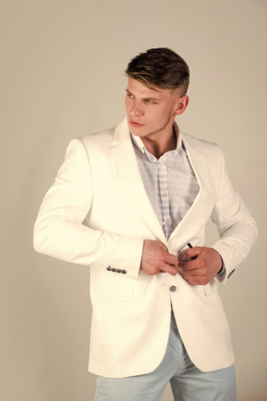Macho buttoning white jacket. Man wearing striped shirt and blue pants. Model posing in casual suit on grey background. Fashion concept Stock Photo