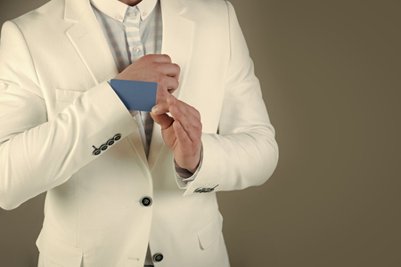 Empty business card in cuff. Businessman in white jacket on grey background. Ace up sleeve concept. Advantage and secret trump. Cheating and trick 스톡 콘텐츠