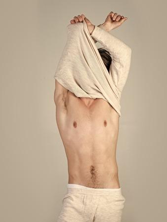 Sleepy man undress on grey background. Morning wake up, everyday life. Mens heals care. Stock Photo