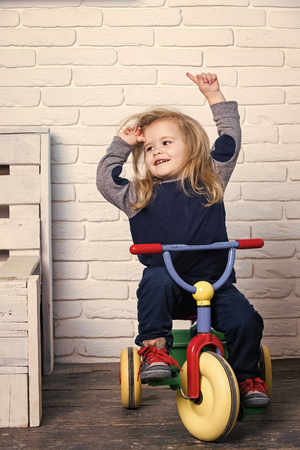 Child smiling on the tricycle. Happy childhood concept. Stock Photo