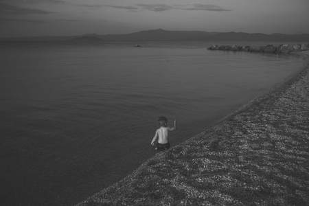 Cute child waving hand at seashore in evening. Boy sits in sea water, rear view. Farewell and parting concept. Toddler on vacation farewells with summer holidays on sunset. Summertime sadness Foto de archivo