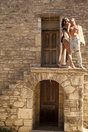 Woman in black lingerie, man with nude torso stands outdoor. Couple enjoys nudity. Sexy couple undressing under sunlight with ancient rocky wall and old door on background. Passion and erotic concept