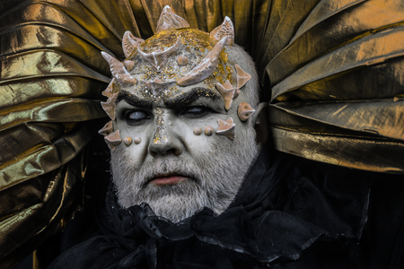 Man with thorns or warts, face covered with glitters. Demon with golden collar on black background. Alien, demon, sorcerer makeup. Fantasy concept. Senior man with white beard dressed like monster.
